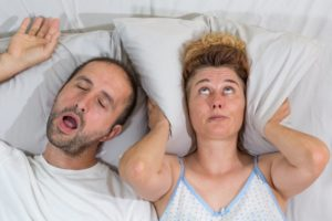 woman covering ears from snoring