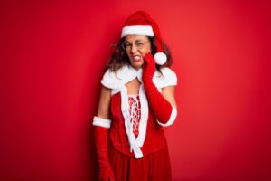 woman in Santa suit with tooth pain