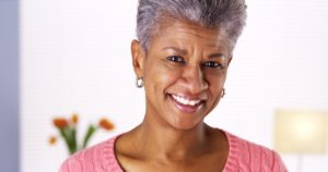 older attractive woman curly grey hair pink shirt