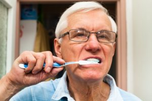 older man brushing teeth preventing dental implant infections